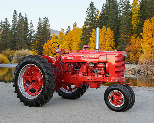 TRA 01 RK0347 01 © Kimball Stock 1938 McCormick Farmall MD Tractor Red 3/4 Side View On Gravel By Pond And Autumn Trees