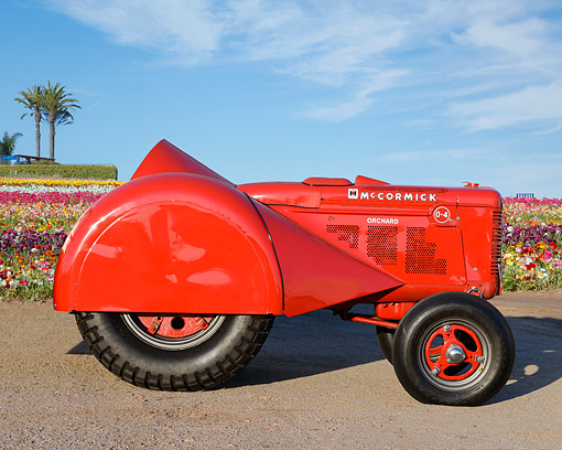 TRA 01 RK0349 01 © Kimball Stock 1941 McCormick Orchard 0-4 Tractor Red Profile View On Gravel By Field Of Flowers