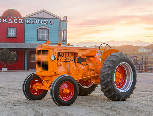 TRA 01 RK0350 01 © Kimball Stock 1959 Minneapolis-Moline G Tractor Orange 3/4 Side View On Gravel By Building At Dusk