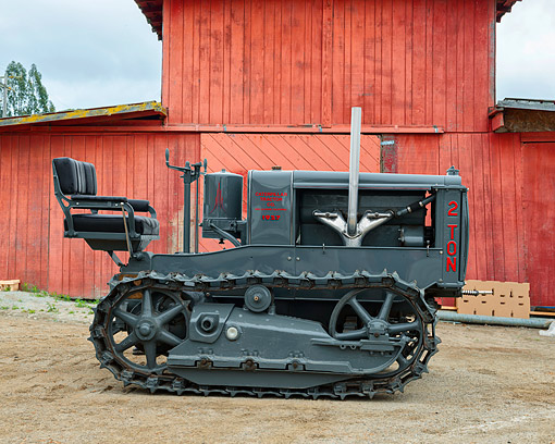 TRA 01 RK0357 01 © Kimball Stock 1927 Caterpillar 2-Ton Tractor Profile View By Barn