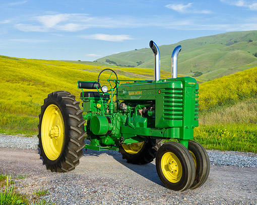 TRA 01 RK0377 01 © Kimball Stock 1942 John Deere G Green Tractor 3/4 Front View In Grassy Hills