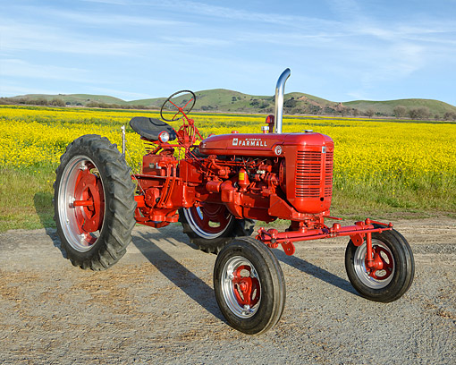 TRA 01 RK0390 01 © Kimball Stock 1952 McCormick Farmall Super C Tractor Red 3/4 Front View By Field Of Flowers