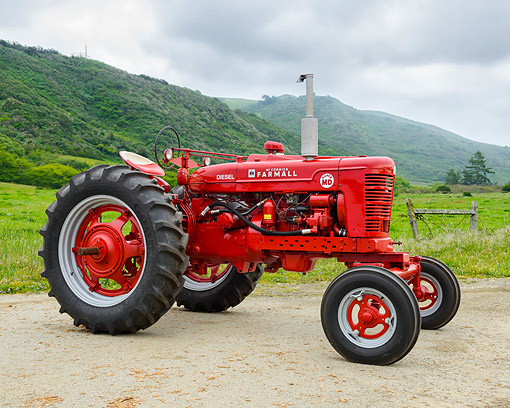 TRA 01 RK0392 01 © Kimball Stock 1953 Farmall Super MD Tractor Red 3/4 Front View On Farm