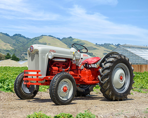 TRA 01 RK0396 01 © Kimball Stock 1954 Ford Jubilee Tractor 3/4 Front View On Farm