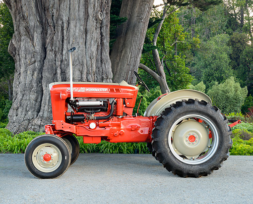 TRA 01 RK0399 01 © Kimball Stock 1960 Ford 541 Workmaster Tractor Red Profile View By Trees