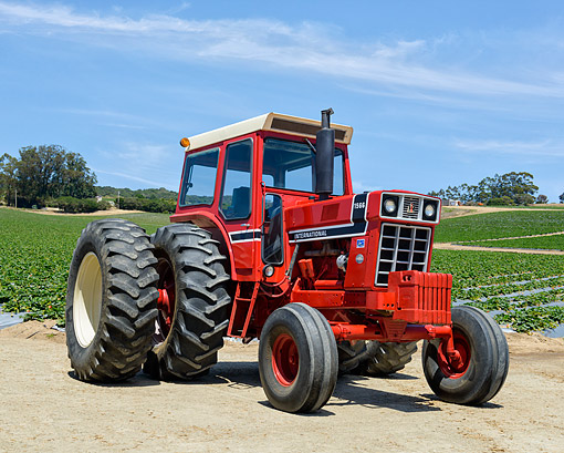 TRA 01 RK0405 01 © Kimball Stock 1975 International Harvester 1566 Tractor Red 3/4 Front View On Farm