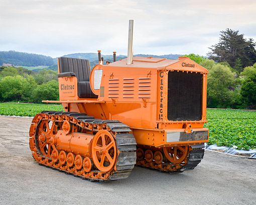 TRA 01 RK0409 01 © Kimball Stock 1932 Cletrac 15 Tractor Orange 3/4 Front View On Farm
