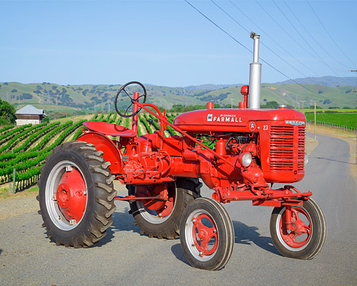 TRA 01 RK0414 01 © Kimball Stock 1941 Farmall A 23 Red 3/4 Front On Road Winding Through Farm Country