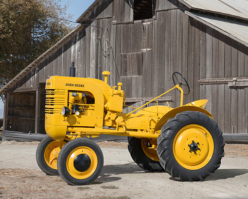 TRA 01 RK0418 01 © Kimball Stock 1942 John Deere LI Tractor Yellow 3/4 Front View By Barn