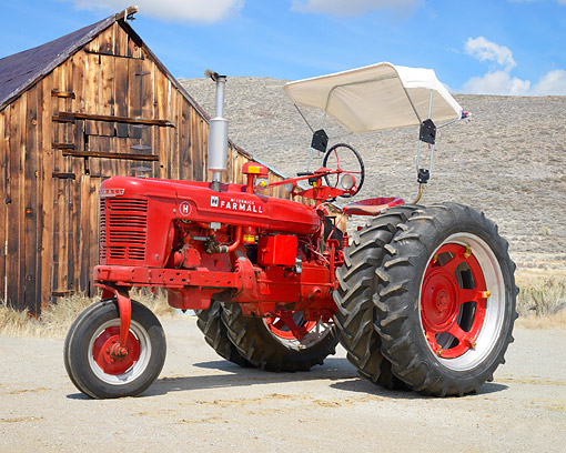 TRA 01 RK0422 01 © Kimball Stock 1949 McCormick Farmall H Tractor Red 3/4 Front View By Barn