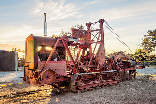 TRA 01 RK0445 01 © Kimball Stock 1928 Cleveland Trencher Baby Digger Red 3/4 Front View On Construction Site At Sunset
