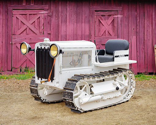 TRA 01 RK0452 01 © Kimball Stock 1928 Caterpillar 15 Tractor White 3/4 Front View By Barn