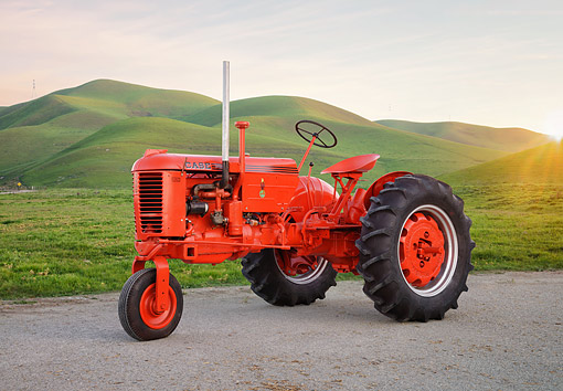 TRA 01 RK0463 01 © Kimball Stock 1942 Case VAC Tractor Red 3/4 Front View By Green Hills At Sunset