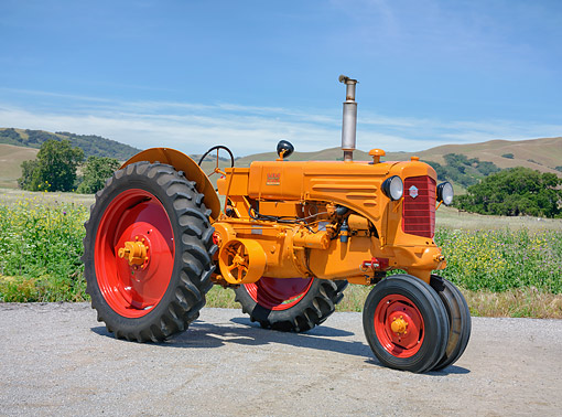 TRA 01 RK0465 01 © Kimball Stock 1946 Minneapolis Moline ZTU Tractor Orange 3/4 Front View By Wildflowers And Distant Hills