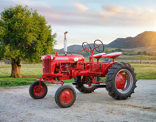 TRA 01 RK0469 01 © Kimball Stock 1950 McCormick-Deering Farmall Cub Two-Seater Red 3/4 Front View On Farm At Sunset