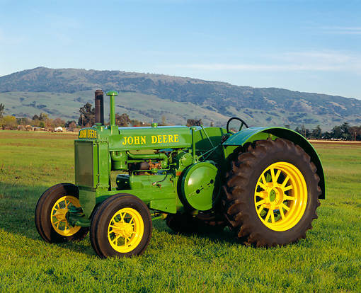 TRA 01 RK0022 02 © Kimball Stock 1935 John Deere Brass Tag Tractor 3/4 Side View On Grass