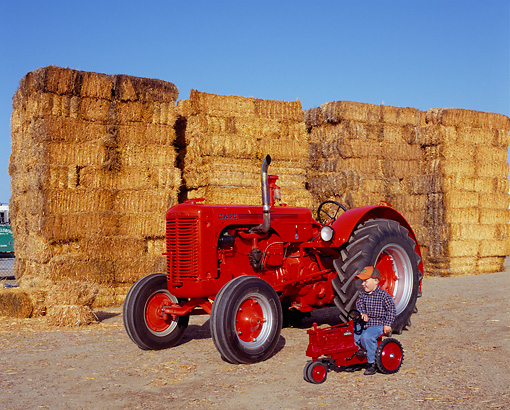 TRA 01 RK0049 04 © Kimball Stock 1947 LA Case Tractor Red 3/4 Front View With Boy On Little Tractor By Hay Stacks