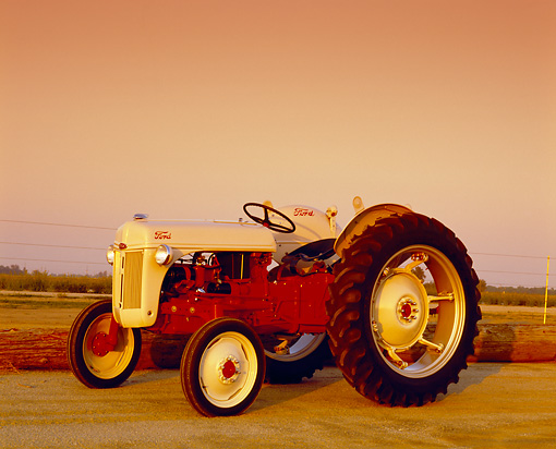 TRA 01 RK0055 03 © Kimball Stock 1948 Ford 8N High Crop Tractor Red And Beige 3/4 Side View On Dirt