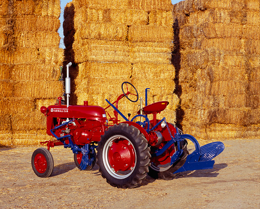 TRA 01 RK0061 02 © Kimball Stock 1948 Farmall Cub Red Tractor 3/4 Side View On Dirt By Stacks Of Hay