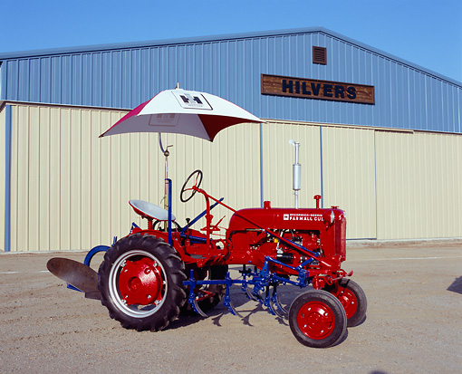 TRA 01 RK0064 01 © Kimball Stock 1948 Farmall Cub Red Tractor With Umbrella 3/4 Side View By Building