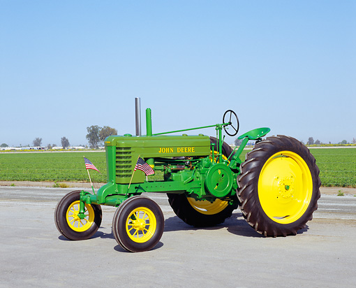 TRA 01 RK0066 04 © Kimball Stock 1943 John Deere B-W Green And Yellow Tractor 3/4 Side View On Pavement Blue Sky