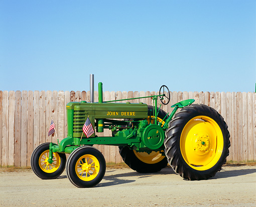 TRA 01 RK0067 04 © Kimball Stock 1943 John Deere B-W Green And Yellow Tractor 3/4 Side View By Fence