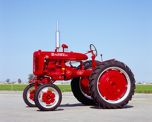 TRA 01 RK0069 07 © Kimball Stock 1940's Farmall AV Red Tractor 3/4 Side View On Pavement Blue Sky