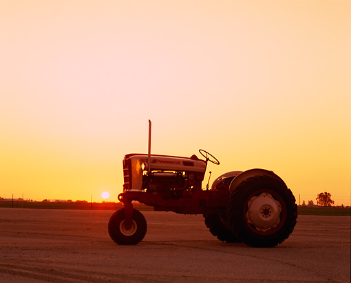 TRA 01 RK0075 01 © Kimball Stock 1958 Ford 961 Red And Beige Tractor Side View On Dirt Sunset