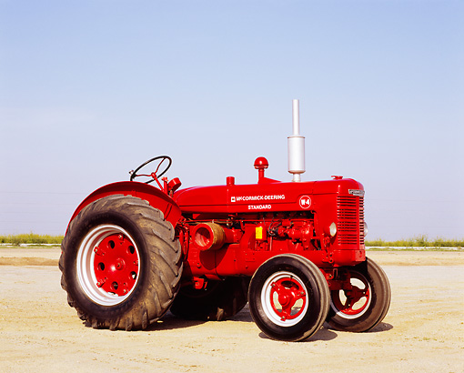 TRA 01 RK0088 02 © Kimball Stock 1947 McCormick Deering W-4 Standard Red Tractor 3/4 Side View On Dirt Blue Sky