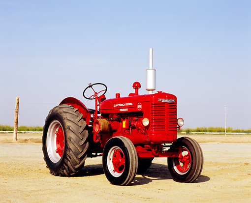 TRA 01 RK0089 01 © Kimball Stock 1947 McCormick Deering W-4 Standard Red Tractor 3/4 Front View On Dirt Blue Sky