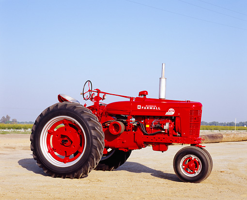 TRA 01 RK0092 03 © Kimball Stock 1954 Farmall Super MTA Red Tractor 3/4 Side View On Dirt Blue Sky
