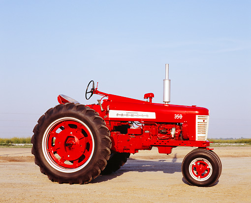 TRA 01 RK0100 02 © Kimball Stock 1958 Farmall 350 Red Tractor Side View On Dirt Blue Sky