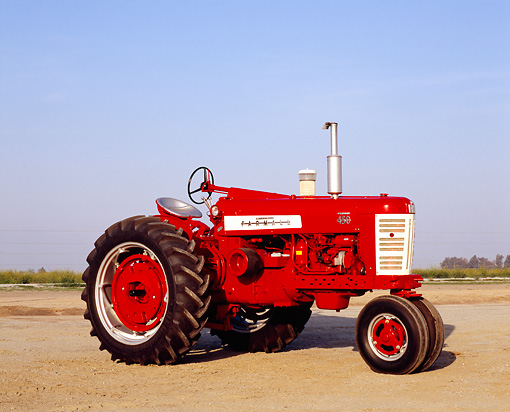 TRA 01 RK0104 04 © Kimball Stock 1957 IH Farmall 450 Red Tractor 3/4 Side View On Dirt Blue Sky