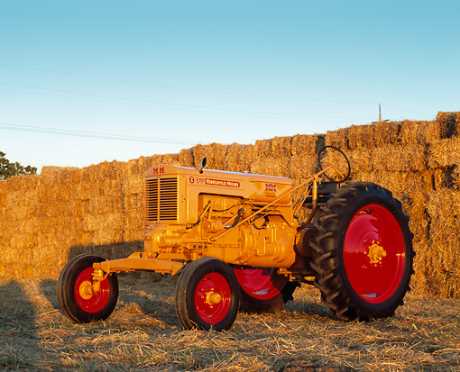 TRA 01 RK0109 03 © Kimball Stock 1949 Minneapolis Moline ZAE Gold Tractor 3/4 Front View By Hay Stacks At Dusk
