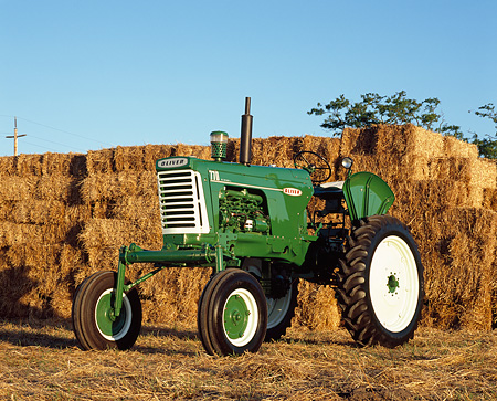 TRA 01 RK0114 02 © Kimball Stock 1960 Oliver 770 Green And White Tractor 3/4 Front By Hay Stacks