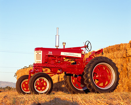 TRA 01 RK0125 01 © Kimball Stock 1958 Farmall 350 High Clearance Red And White 3/4 Low Side View By Hay Stacks