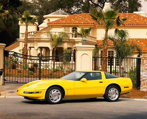 VET 01 RK0066 09 © Kimball Stock 1995 Chevrolet Corvette Yellow 3/4 Side View On Pavement By House