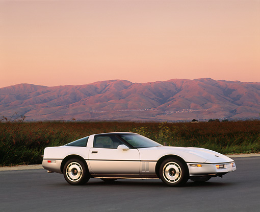 VET 01 RK0306 01 © Kimball Stock 1985 Chevrolet Corvette 3/4 Side View On Pavement By Tall Grass Mountains Background At Dusk