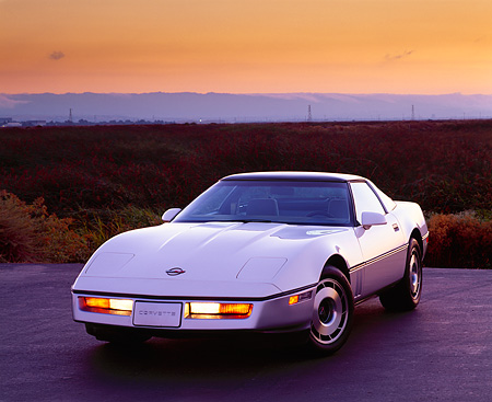VET 01 RK0307 05 © Kimball Stock 1985 Chevrolet Corvette White 3/4 Front View On Pavement By Tall Grass Mountains Background Parking Lights On
