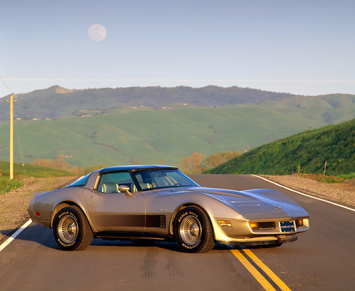 VET 01 RK0447 02 © Kimball Stock 1982 Chevrolet Corvette Crossfire Injection Gold Side 3/4 View On Road Hills Background