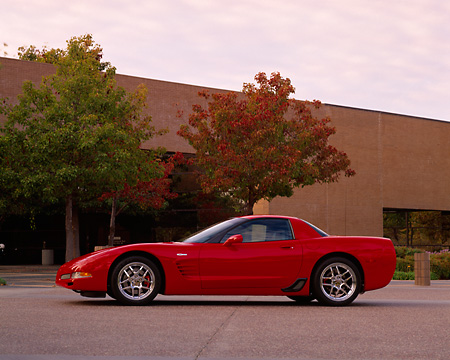 VET 01 RK0622 02 © Kimball Stock 2004 Chevrolet Corvette Z06 Red Profile View On Pavement By Building