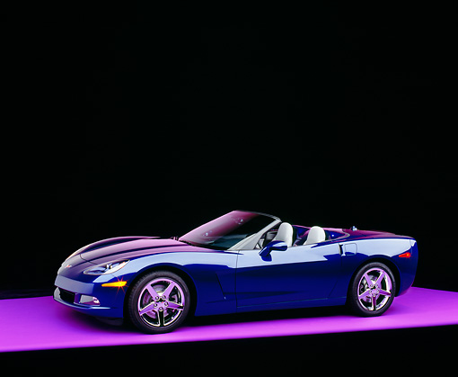 VET 01 RK0693 08 © Kimball Stock 2005 Chevrolet Corvette C6 Convertible Blue 3/4 Side View On Purple Floor Studio