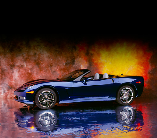 VET 01 RK0698 08 © Kimball Stock 2005 Chevrolet Corvette C6 Convertible Blue 3/4 Side View On Mylar Floor Sunburst Background