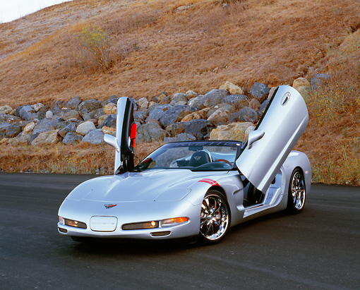 VET 01 RK0719 03 © Kimball Stock 2001 Chevrolet Corvette Convertible Silver 3/4 Front View Doors Up On Pavement