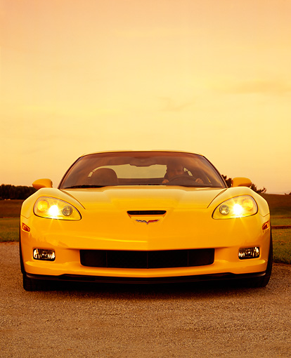 VET 01 RK0731 03 © Kimball Stock 2006 Chevrolet, Corvette, Z06, Yellow Low Head On View With Driver On Pavement By Grass