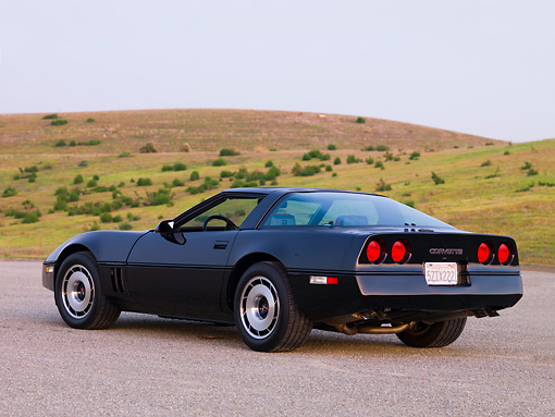 VET 01 RK0818 01 © Kimball Stock 1984 Chevrolet Corvette Coupe Black 3/4 Rear View On Pavement By Hill Blue Sky