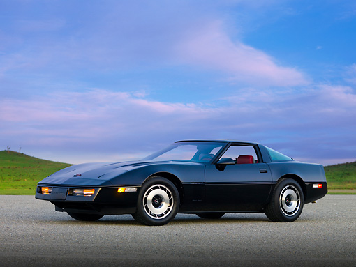 VET 01 RK0824 01 © Kimball Stock 1984 Chevrolet Corvette Coupe Black 3/4 Front View On Pavement By Hill Blue Sky