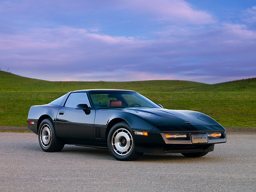 VET 01 RK0825 01 © Kimball Stock 1984 Chevrolet Corvette Coupe Black 3/4 Front View On Pavement By Hill Blue Sky