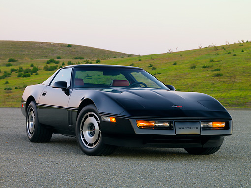 VET 01 RK0826 01 © Kimball Stock 1984 Chevrolet Corvette Coupe Black 3/4 Front View On Pavement By Hill Blue Sky