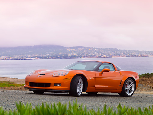 VET 01 RK0845 01 © Kimball Stock 2008 Chevrolet Corvette Z06 Orange 3/4 Front View On Road By Water